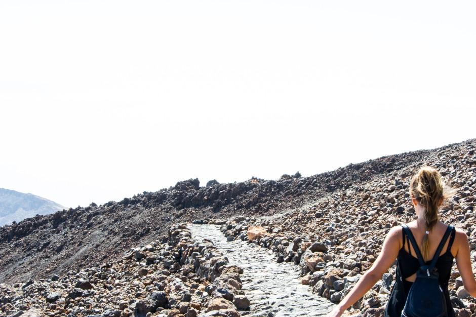 Mujer andando en una montaña con piedras